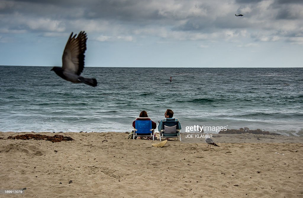 A couple rests on the beach late afternoon at Laguna Beach, California on June 3, 2012.