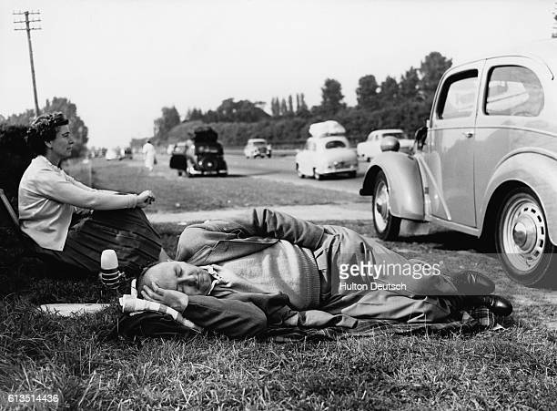 A couple rests on the lawn along the side of the Exeter ByPass