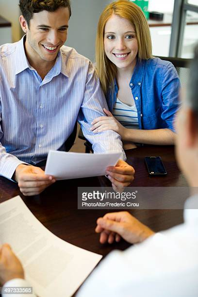Couple reviewing paperwork in meeting with advisor