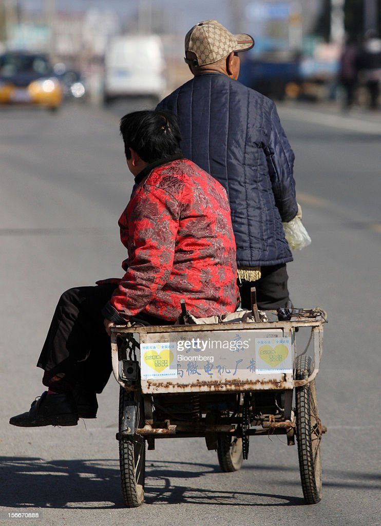 A couple rides a bicycle on a street in Pinggu, on the outskirts of Beijing, China, on Saturday, Nov. 17, 2012. China's gross domestic product slowed to 7.4 percent in the July-September period from a year earlier, the weakest in three years. Photographer: Tomohiro Ohsumi/Bloomberg via Getty Images
