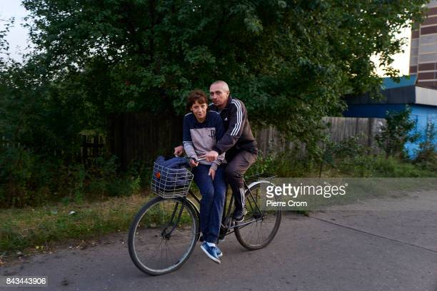 A couple rides a bicycle on September 06 2017 in Avdiivka Ukraine The frontlinecity Avdiivka is located on the outskirsts of Donetsk and remains a...