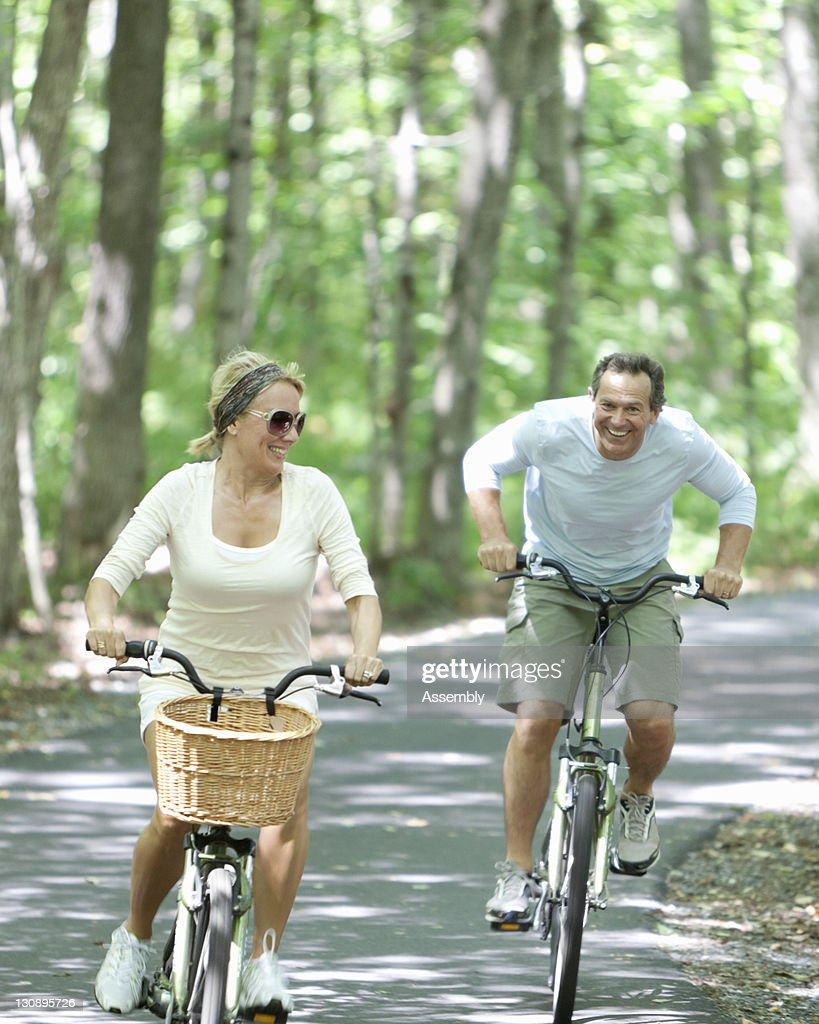 Couple rides bikes on tree lined path : Stock Photo