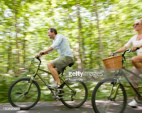 Couple rides bikes on tree lined street : Foto de stock