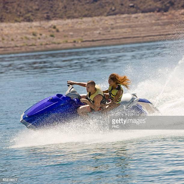 Couple rides jet ski