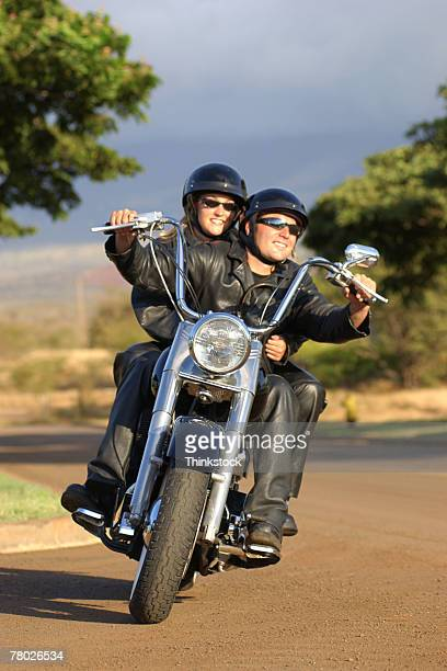 A couple rides their motorcycle on a curvy road toward the viewer.