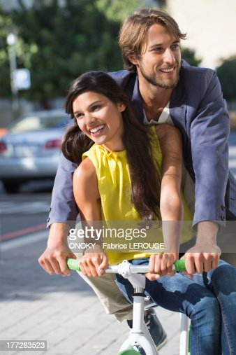 Couple riding a bicycle and smiling : Foto de stock