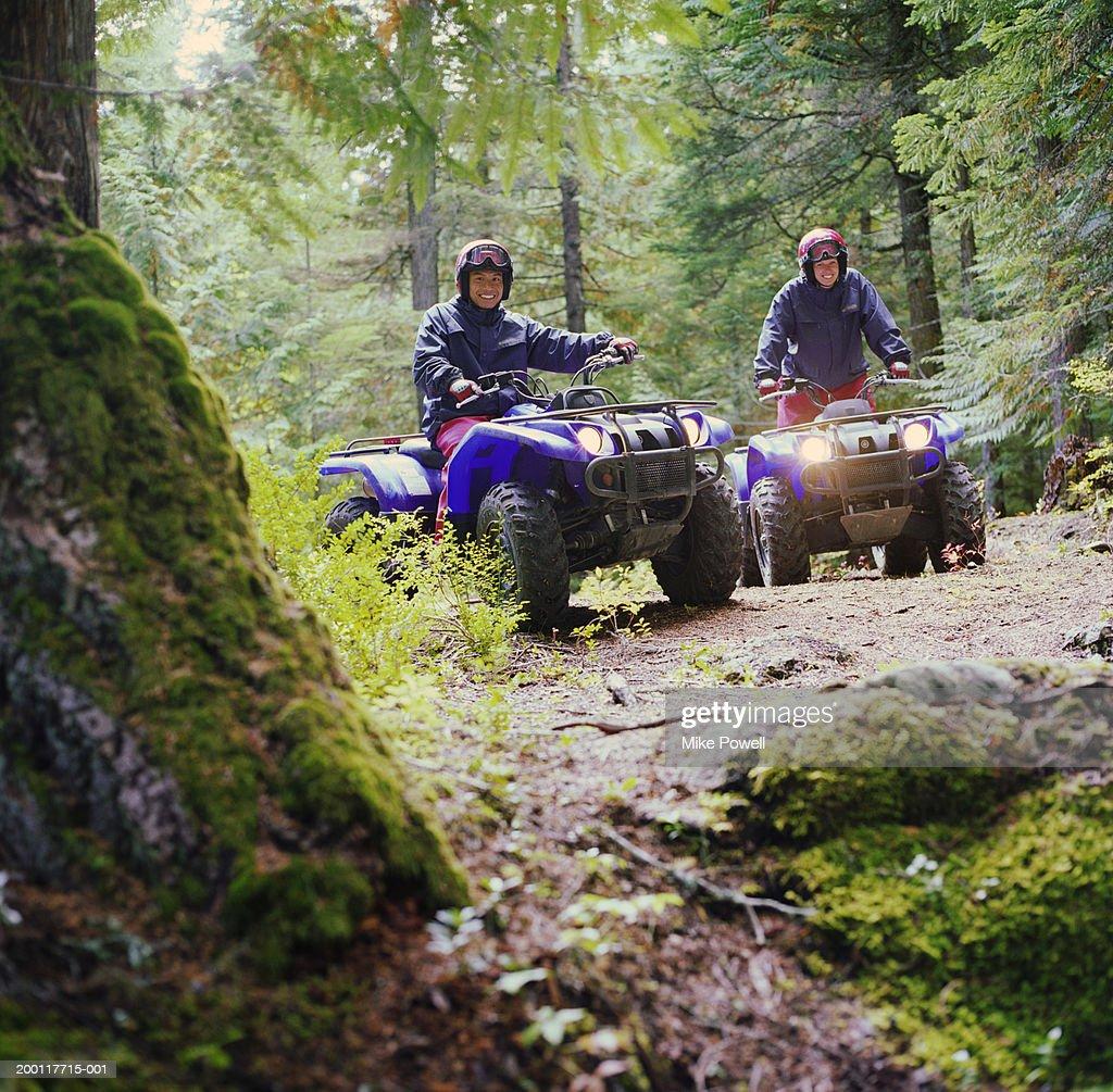 Couple riding ATV's through forest, portrait