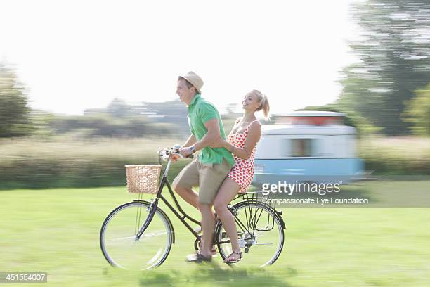 Couple riding bicycle in countryside