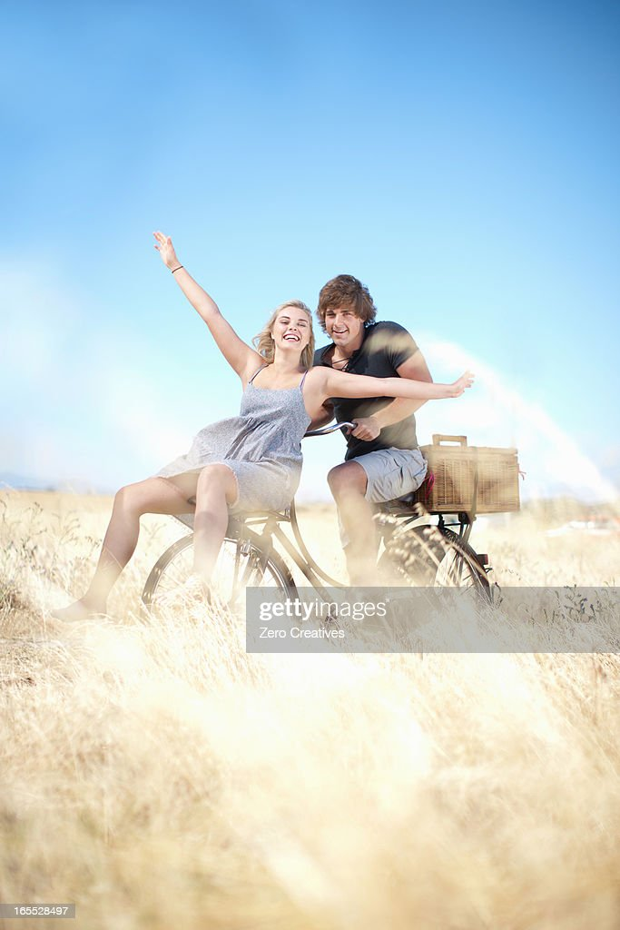 Couple riding bicycle in tall grass : Stock Photo
