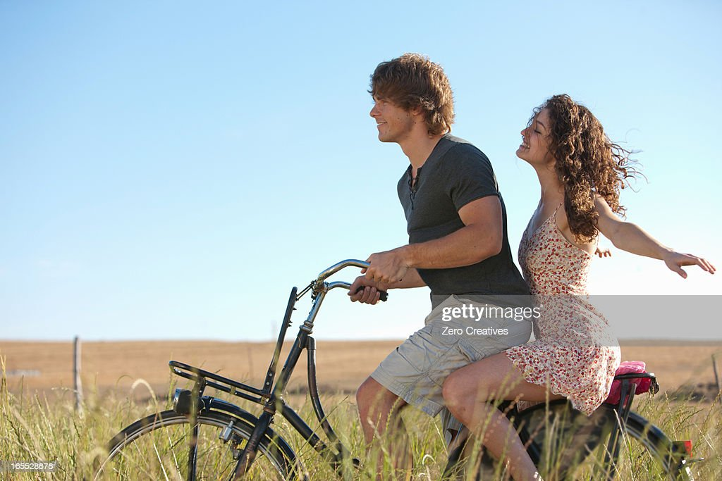 Couple riding bicycle in tall grass : Foto stock