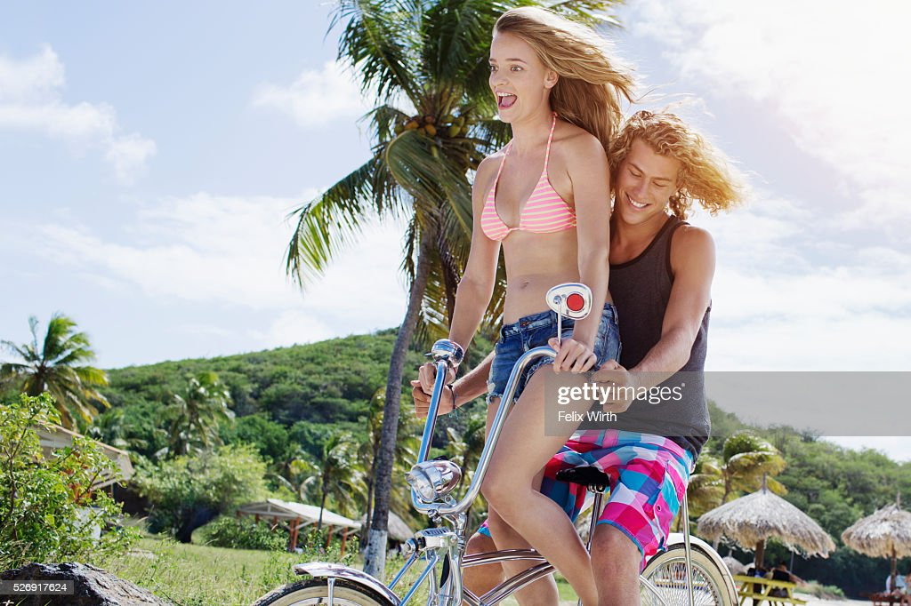 Couple riding bicycle on beach : Photo