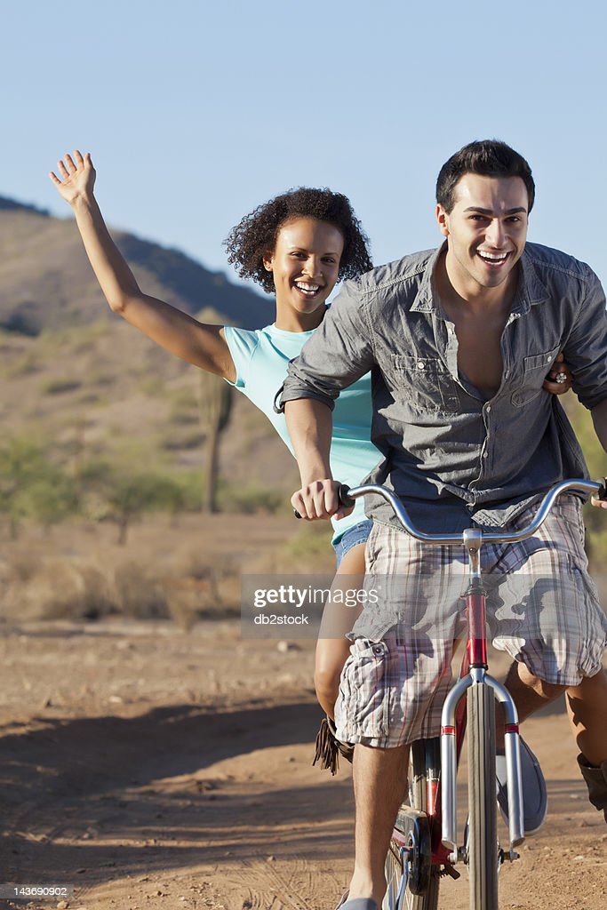 Couple riding bicycle on dirt road : Stock Photo