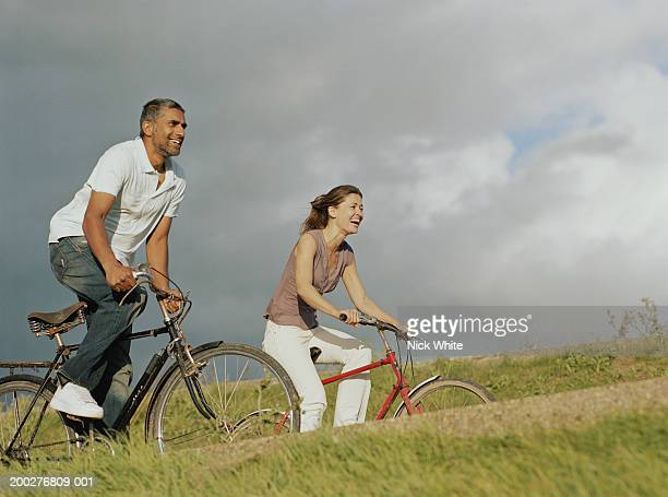 Couple riding bicycles along path by grassy bank, laughing