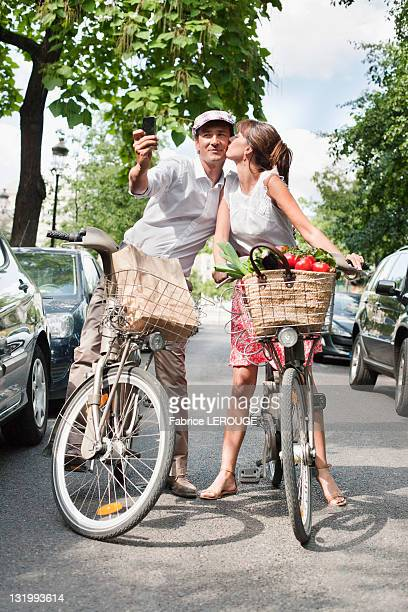Couple riding bicycles and taking a picture of themselves with a mobile phone, Paris, Ile-de-France, France
