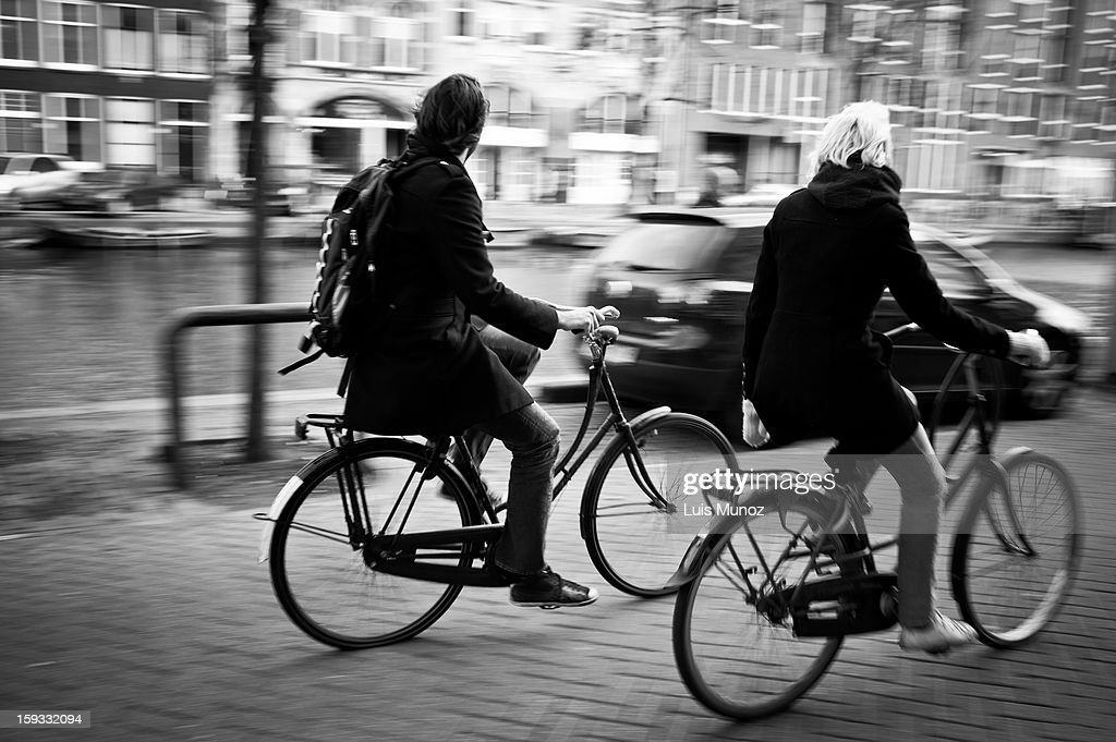 CONTENT] A couple riding bicycles in Prinsengracht. Amsterdam, Netherlands.