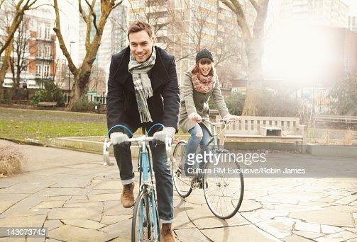 Couple riding bicycles in urban park : ストックフォト