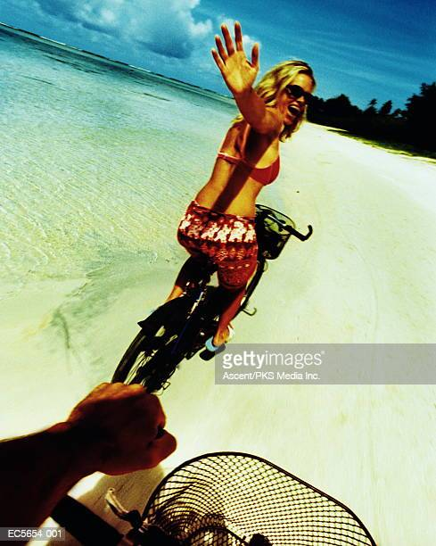 Couple riding bicycles on beach, woman waving (cross-processed)