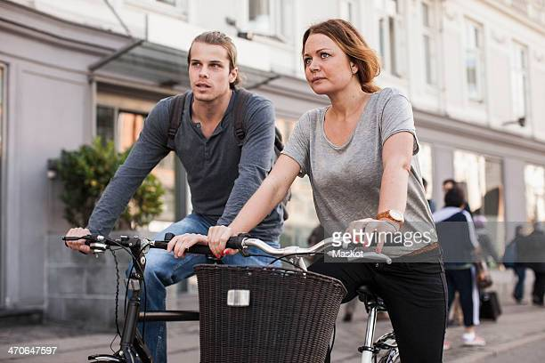 Couple riding bicycles on city street