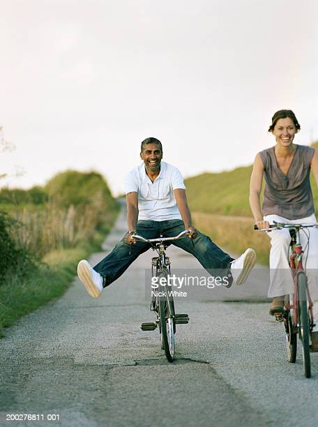 Couple riding bicycles on path, man balancing with outstretched legs