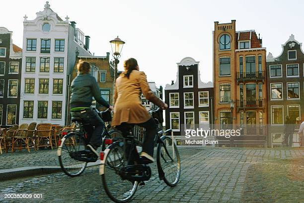Couple riding bicycles, rear veiw (blurred motion)