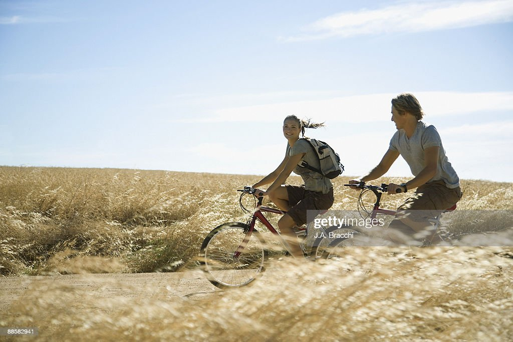 Couple riding bicycles through countryside