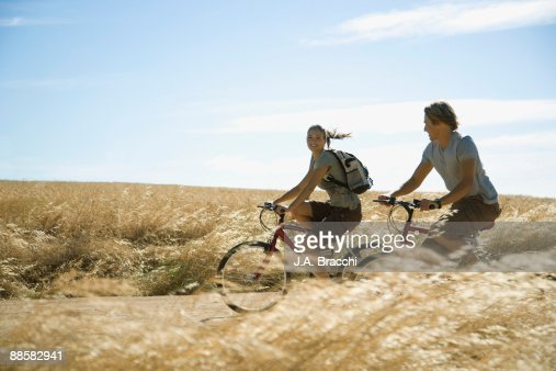 Couple riding bicycles through countryside : Stock Photo
