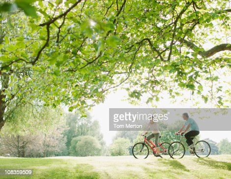 Couple riding bicycles underneath tree : Stock Photo