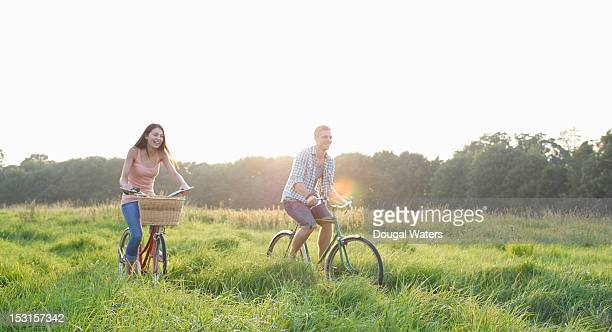 Couple riding bikes in countryside.