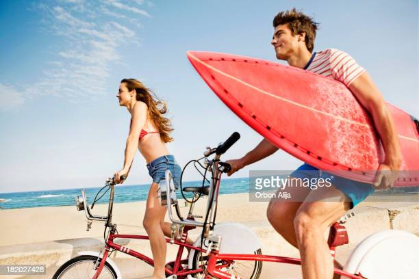 Couple riding bikes on beach boardwalk