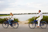 Couple riding bikes on road by water