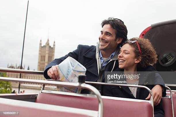 Couple riding double decker bus past Parliament Building in London