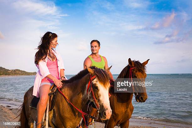 Couple riding horses at sunset