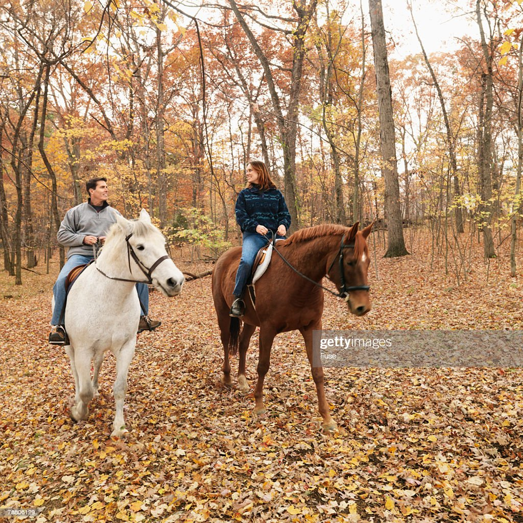Couple Riding Horses in Woods