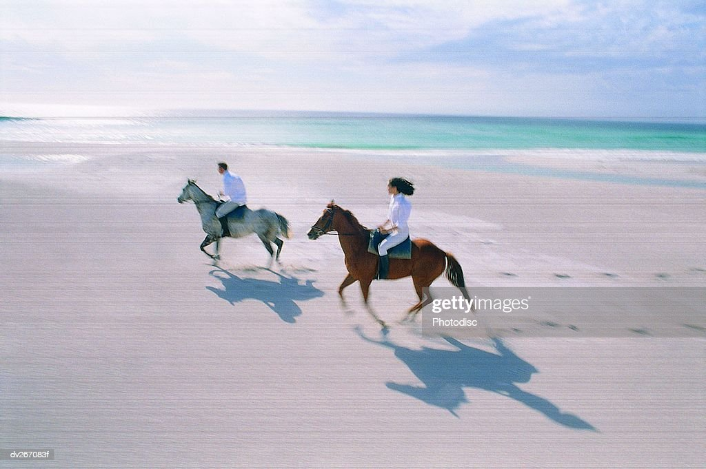 Couple riding horses on beach