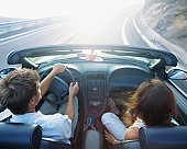 Couple riding in convertible car on highway, elevated, rear view