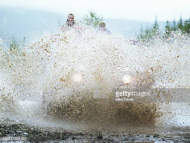 Couple riding in off road vehicle, driving through large mud puddle