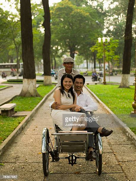 Couple riding in pedal cab together, Vietnam
