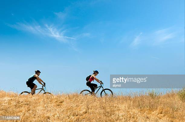 Couple Riding Mountain Bikes on a Trail