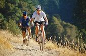 Couple riding mountain bikes on dirt trail