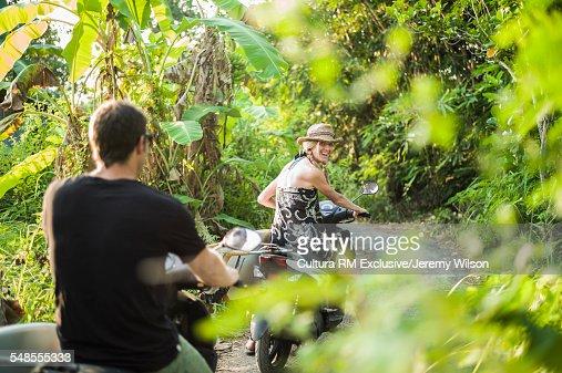 Couple riding on motorbikes through forest, Nusa Lembongan, Indonesia
