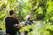 Couple riding on motorbikes through forest, Nusa Lembongan, Indonesia