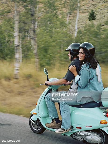 Couple riding on scooter on country road, smiling