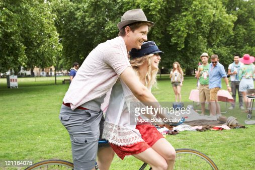 couple riding one bicycle through the park : Stock Photo