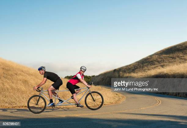 Couple riding opposing tandem bicycle on rural road