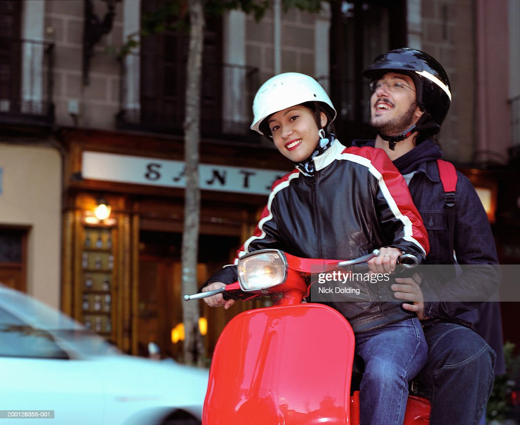 Couple riding scooter in city street, portrait of woman : Stock Photo