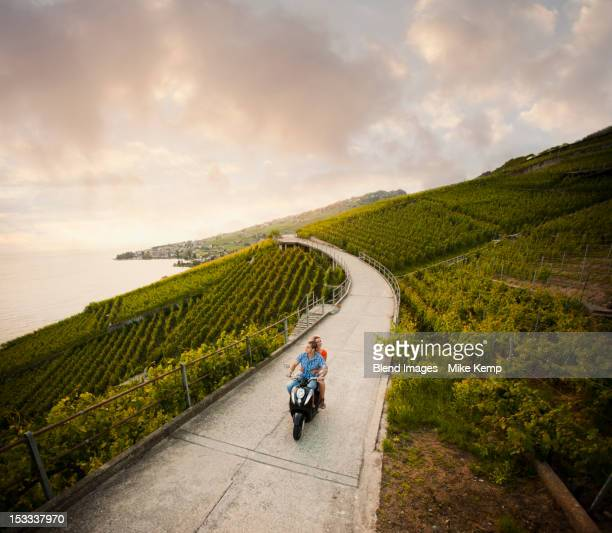Couple riding scooter in vineyard
