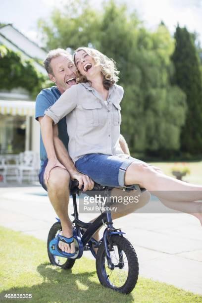 Paar Reiten Fahrräder in grass kleine