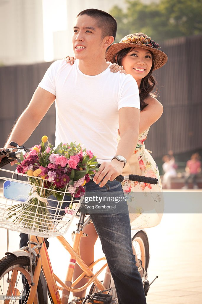Couple Riding Tandem Bicycle Flowers in Basket : Stock Photo