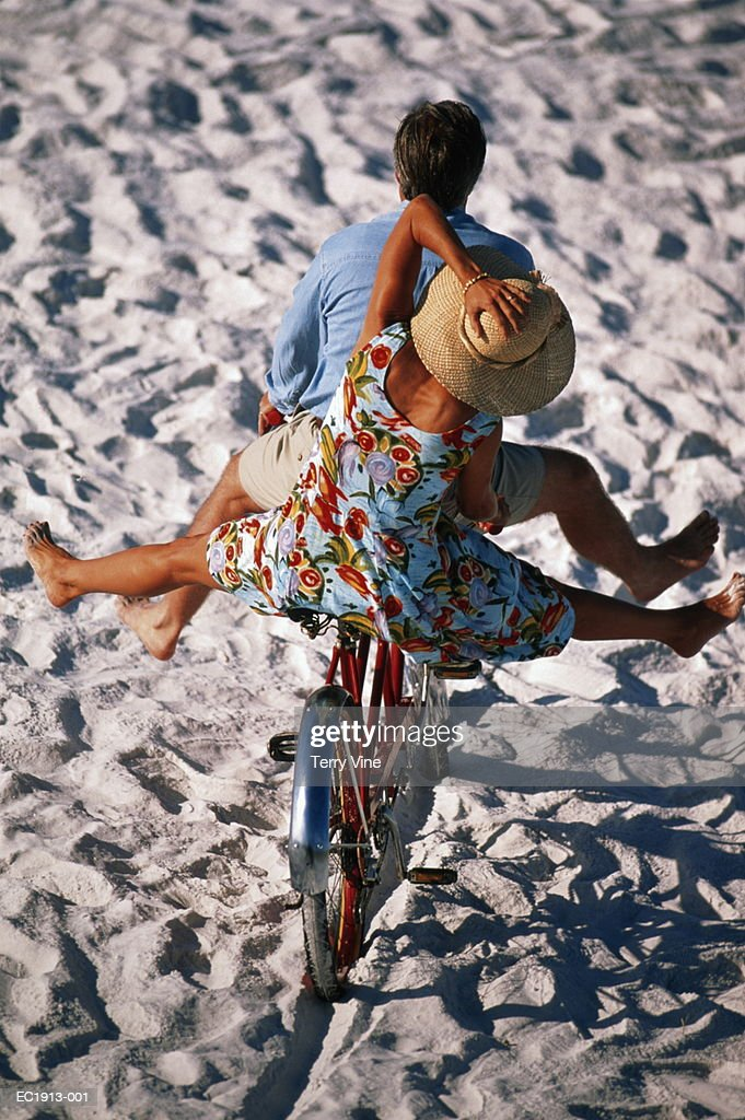 Couple riding tandem bicycle on beach, elevated view : Stock Photo