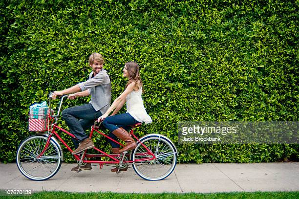 Couple riding tandem bike in front of hedge